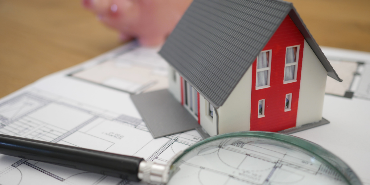 Image of a house model with a magnifying glass next to it